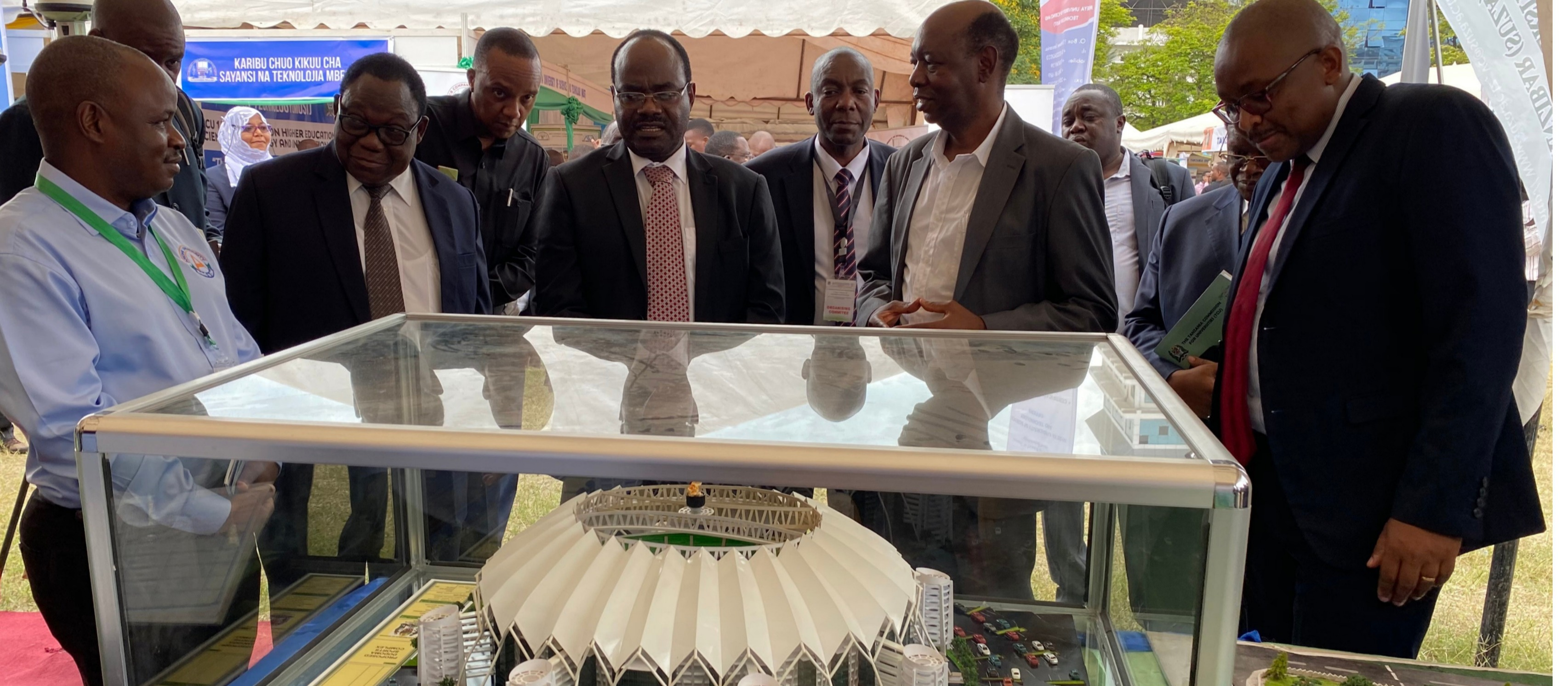 The Permanent Secretary for the Ministry of Education, Science and Technology Dr. Leonard Akwilapo shares a light moment with Ardhi University team while viewing a proposed Dodoma sports complex model designed by Ardhi University shortly after visiting exhibitors' pavilions during the opening ceremo...